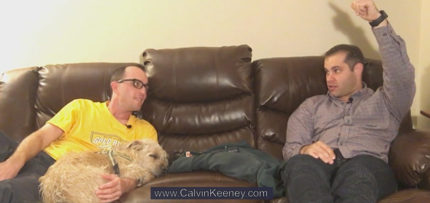 Calvin Keeney holding his dog named Nasus (terrier mix) on the couch while talking to Justen Aguillon who is also sitting on the couch