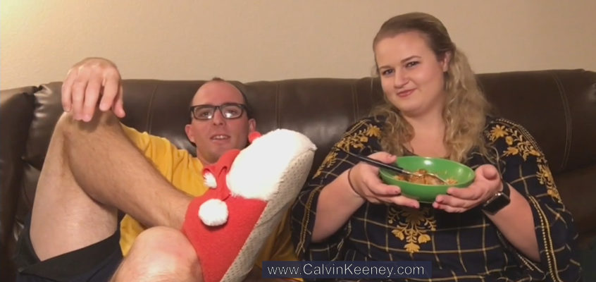 Calvin Keeney sitting on the couch with his legs crossed while wearing santa slippers. Peyton Zipoy is next to him eating food out of a green bowl.