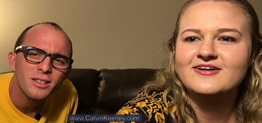 Calvin Keeney staring at the camera while sitting on the couch next to Peyton Zipoy who is working with the Camera