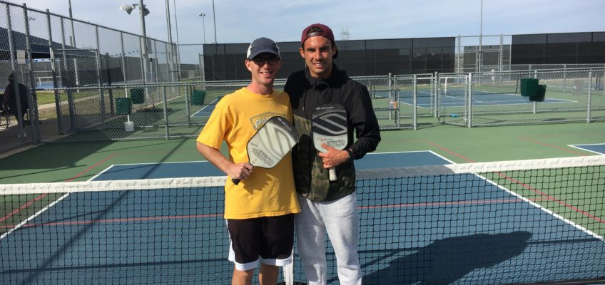 Calvin Keeney in a yellow shirt holding a Pickleball Paddle next to Tyson McGuffin in a black jacket holding a Pickleball Paddle