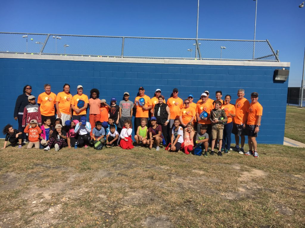 A group of adults in orange shirts that just taught a group of kids from Young Voices of Austin the game of Pickleball in Austin Texas.