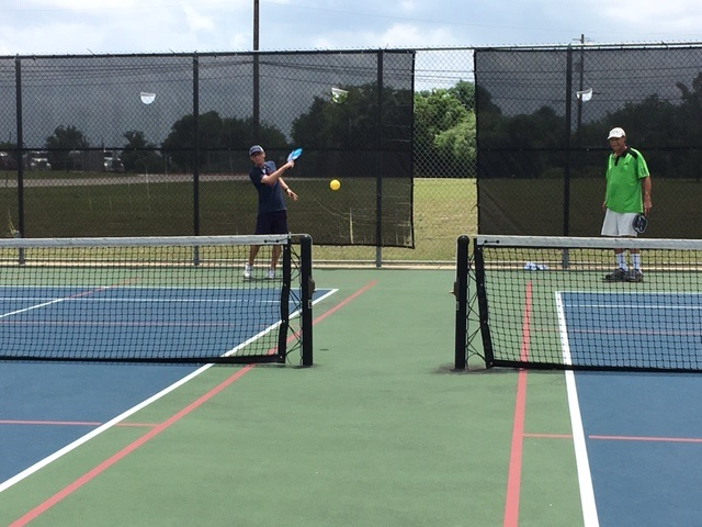 Pickleball Player hitting the ball in between the nets