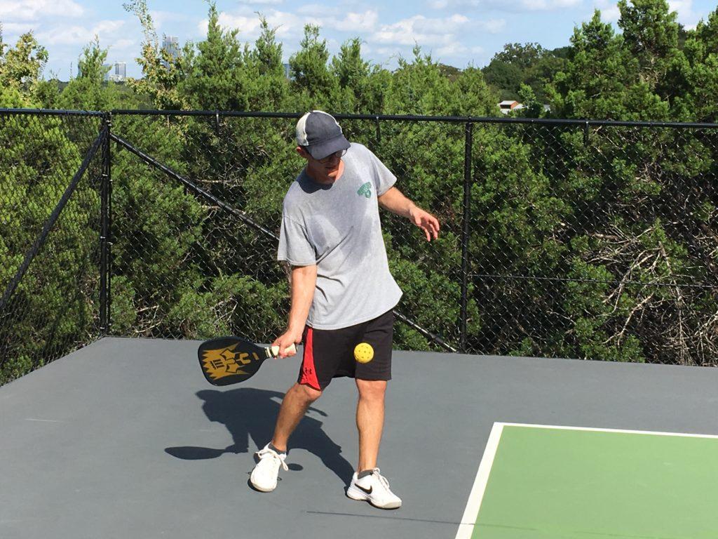 Calvin Serving the Pickleballball wearing a gray shirt