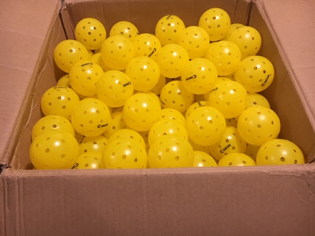 A shipping box full of about 250 USAPA approved C DRIVE Pickleballs