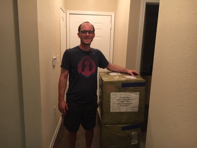 Calvin Keeney standing next to shipping boxes full of C DRIVE Pickleballs and some Paddles