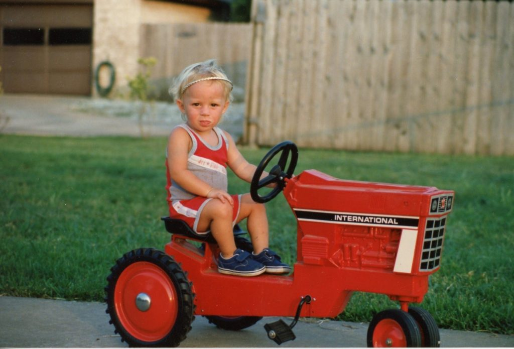 Calvin Keeney sitting on a small red tractor while driving it and looking at the camera. He was about 4 years old