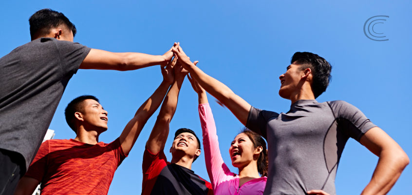 5 people putting their hands up and together as if to show good teamwork