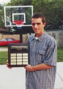 "Calvin Keeney holding his ""Defensive Player of the Year Award"" that he won two times in High School. He is in front of his basketball goal at his home driveway"