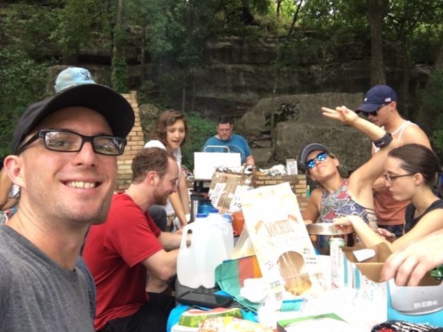 A group of rock climbers outdoors at a picnic table eating food together. Calvin Keeney sitting next to Brian Adrian with Alexa waving at the Camera while Jeremy cooks. Along with 3 other people